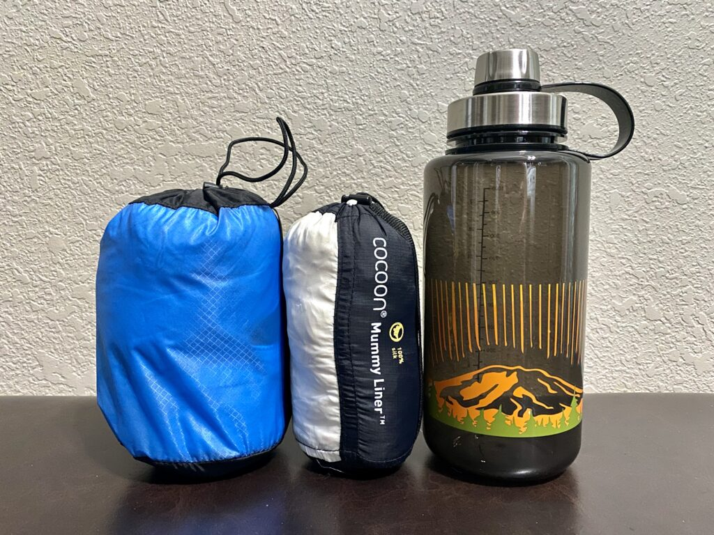 Comparing sleeping bag liner sizes next to a water bottle
