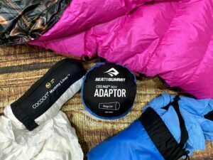sleeping bag liners next to a quilt